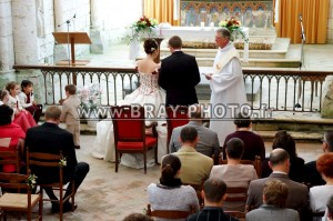 les mariés vus en hauteur de dos devant le prêtre